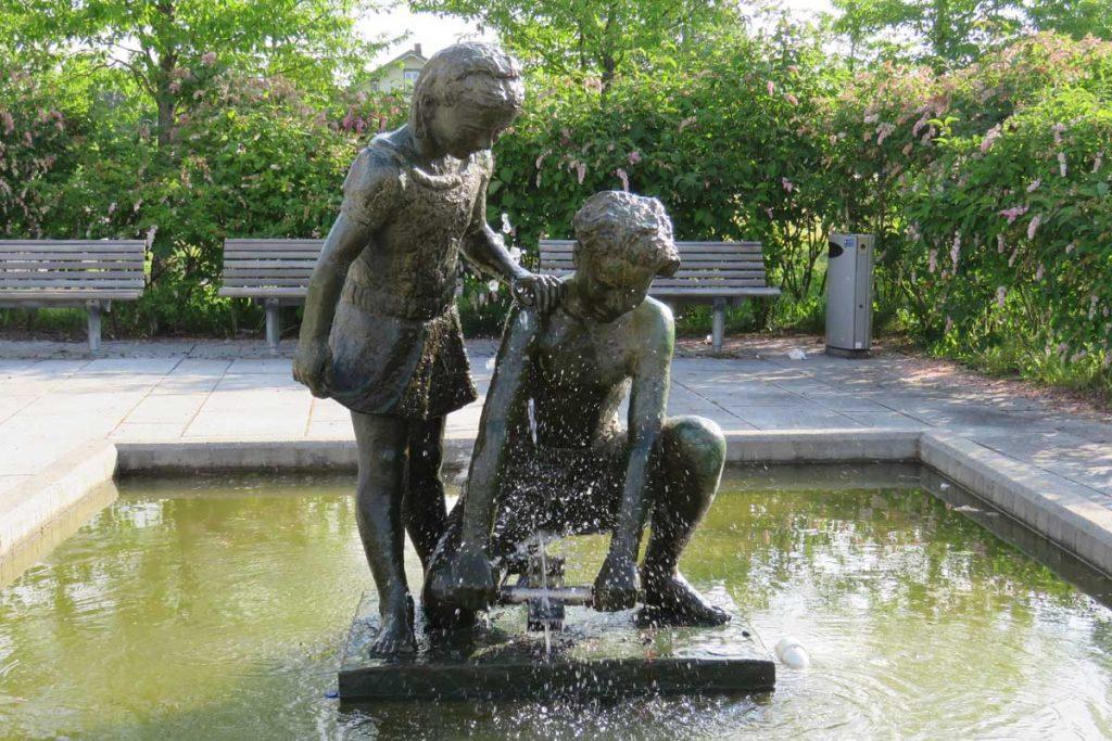 Strømmen i bilder - Strømmen stasjon, vannfontene Vasshjulet, bronsestatue. Foto: Vårt Strømmen, vartstrommen.no.